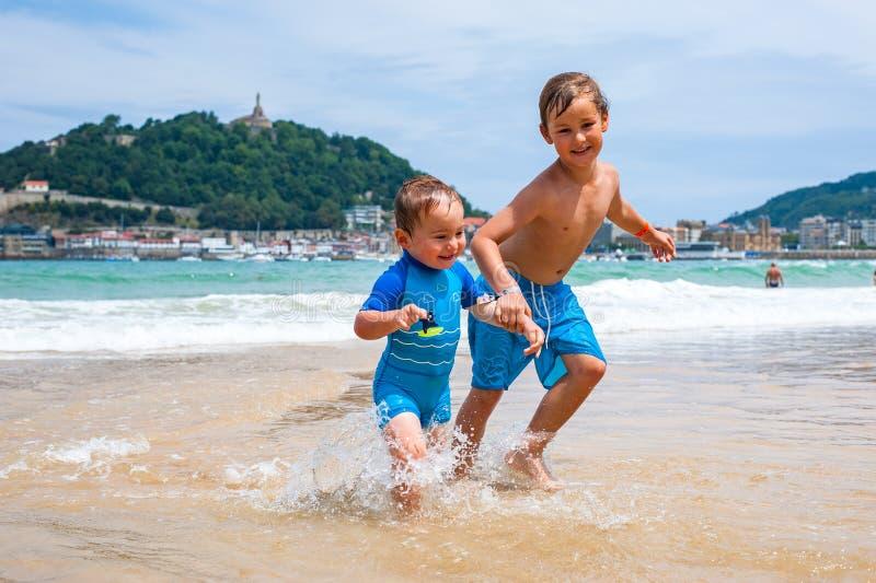 Due ragazzi felici nel funzionamento lungo una spiaggia che rende grande spruzza fotografie stock libere da diritti