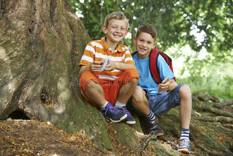 Due ragazzi Geocaching in terreno boscoso fotografie stock
