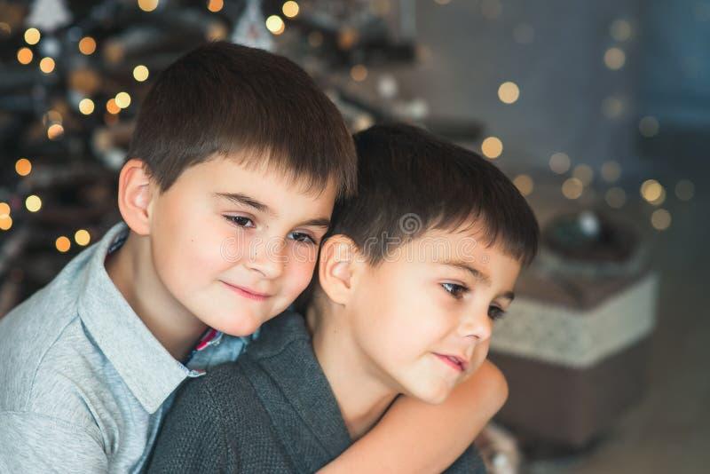 Due ragazzi - i fratelli abbracciano su un fondo delle luci di Natale nuovo fotografia stock
