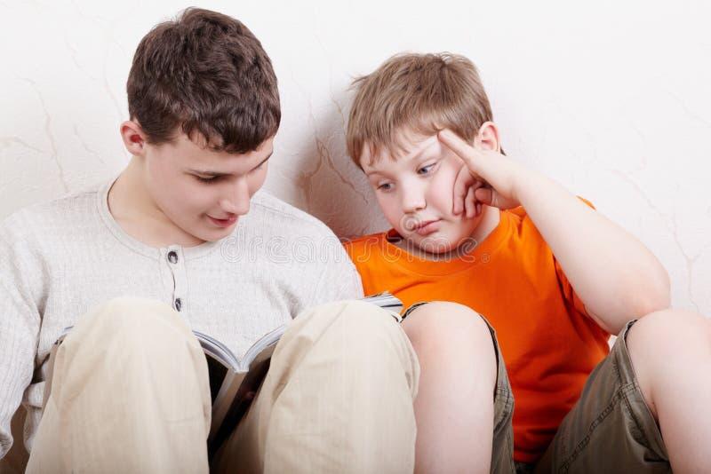 Due ragazzi si siedono e leggono fotografia stock libera da diritti