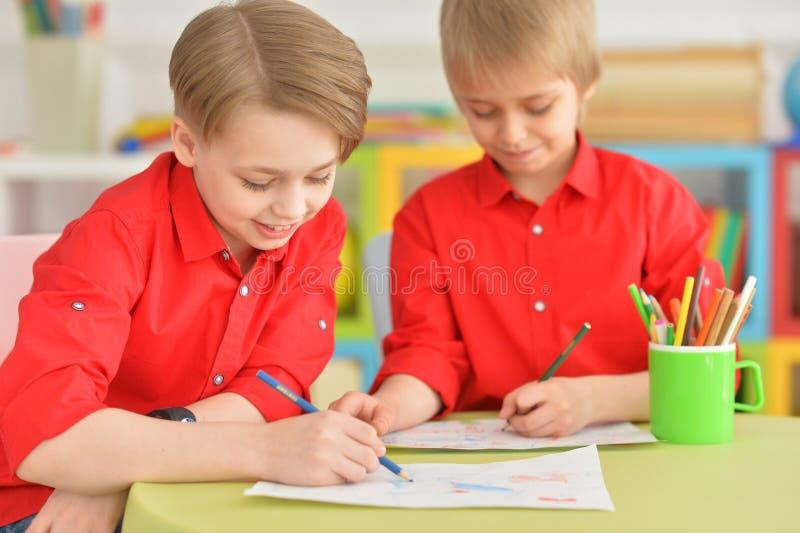 Due ragazzi sorridenti in camice rosse che disegnano con le matite immagine stock