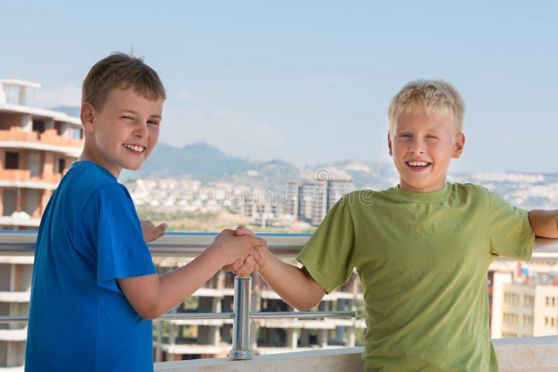 Due ragazzi sorridenti in magliette sono stringono le mani immagine stock libera da diritti