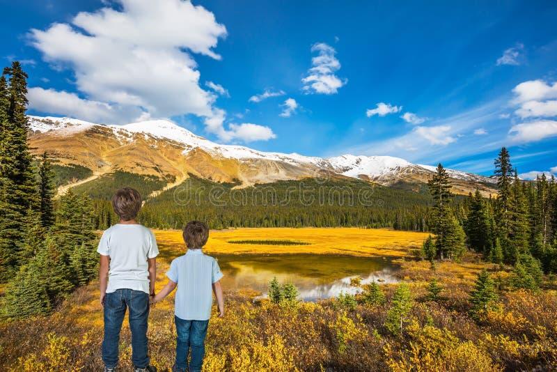 Due ragazzi stanno sulla costa del lago paludoso fotografia stock
