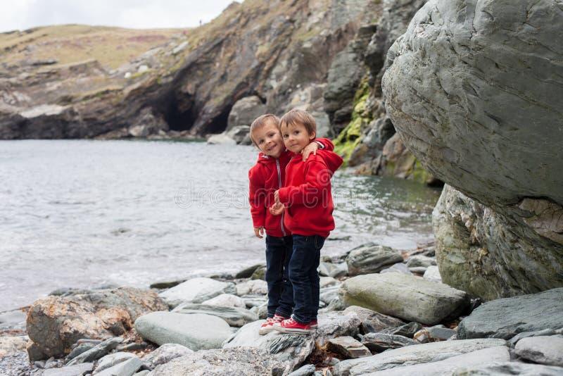 Due ragazzi sulla costa dell'oceano, esaminante la macchina fotografica, smili fotografia stock