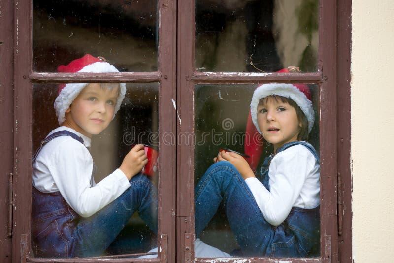 Due ragazzi svegli, fratelli, guardando attraverso una finestra, S aspettante fotografia stock libera da diritti