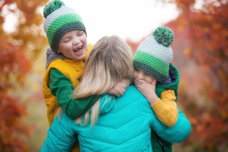 Due ragazzini abbracciano delicatamente sua madre Una passeggiata nel legno di autunno fotografia stock