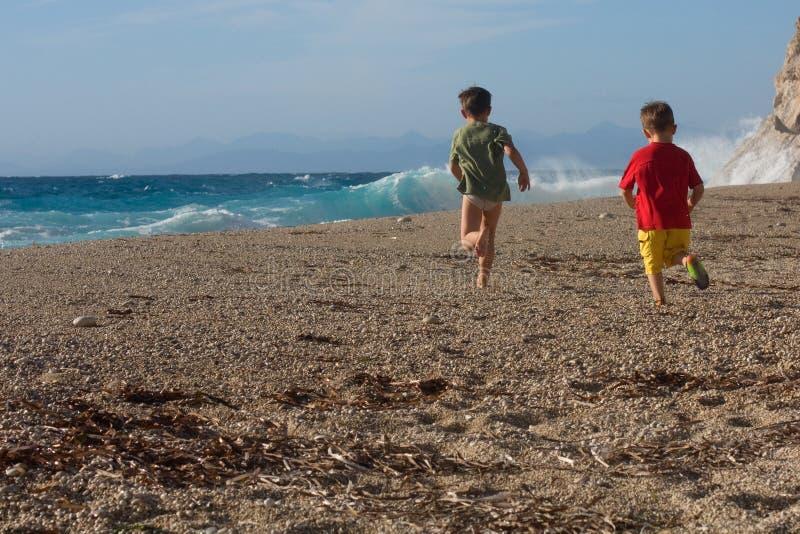 Due ragazzini che funzionano sulla spiaggia immagini stock