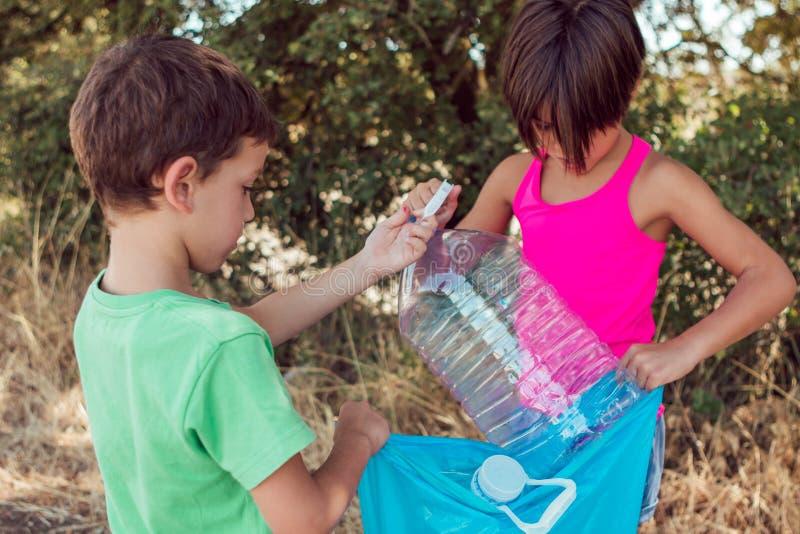 Due ragazzini che raccolgono una bottiglia bevente mentre tengono i rifiuti di plastica nella foresta prendono la cura del concet fotografie stock