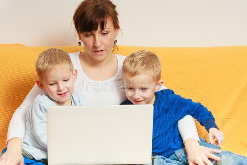 Due ragazzini e madre che per mezzo del computer portatile fotografia stock libera da diritti
