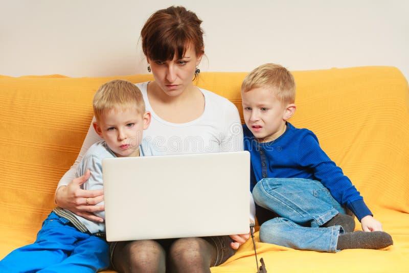 Due ragazzini e madre che per mezzo del computer portatile fotografia stock