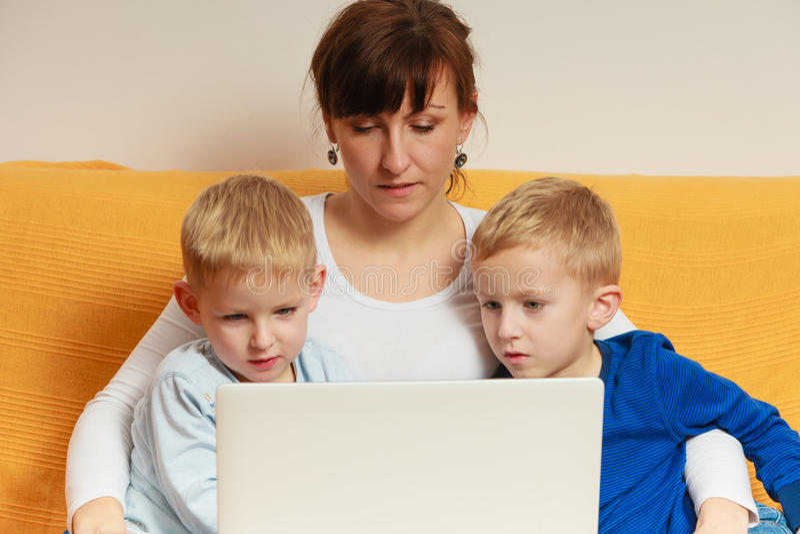 Due ragazzini e madre che per mezzo del computer portatile immagini stock libere da diritti