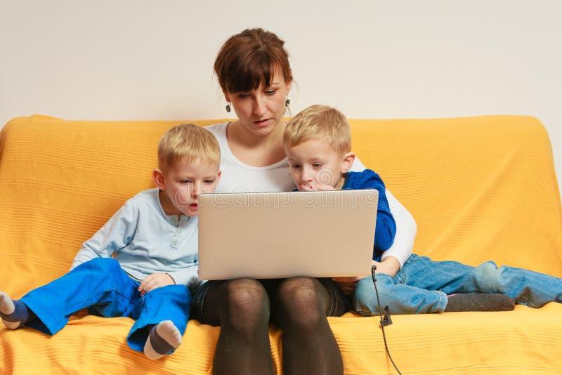Due ragazzini e madre che per mezzo del computer portatile fotografie stock