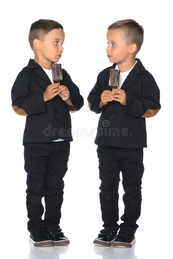 Due ragazzini mangiano il gelato su un bastone fotografia stock