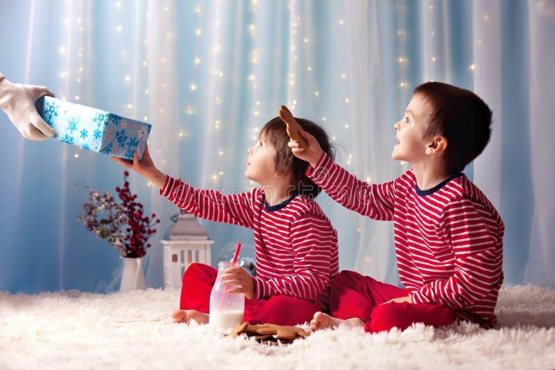 Due ragazzini in pigiami, aspettanti da Santa Claus, brin di Santa fotografie stock libere da diritti