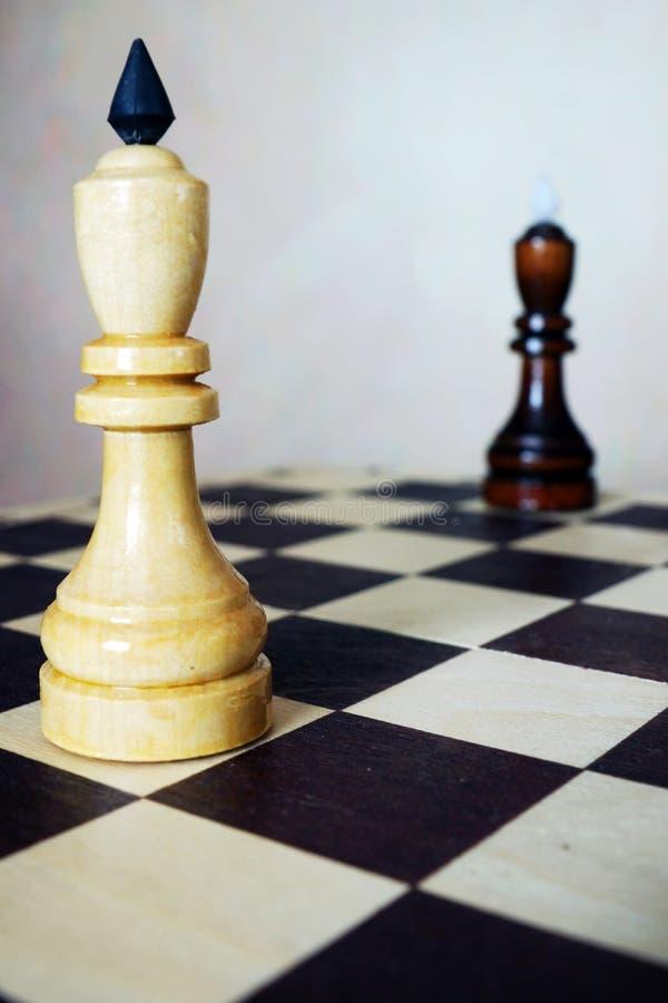 Due re di scacchi stanno dai lati opposti di una scacchiera fotografia stock