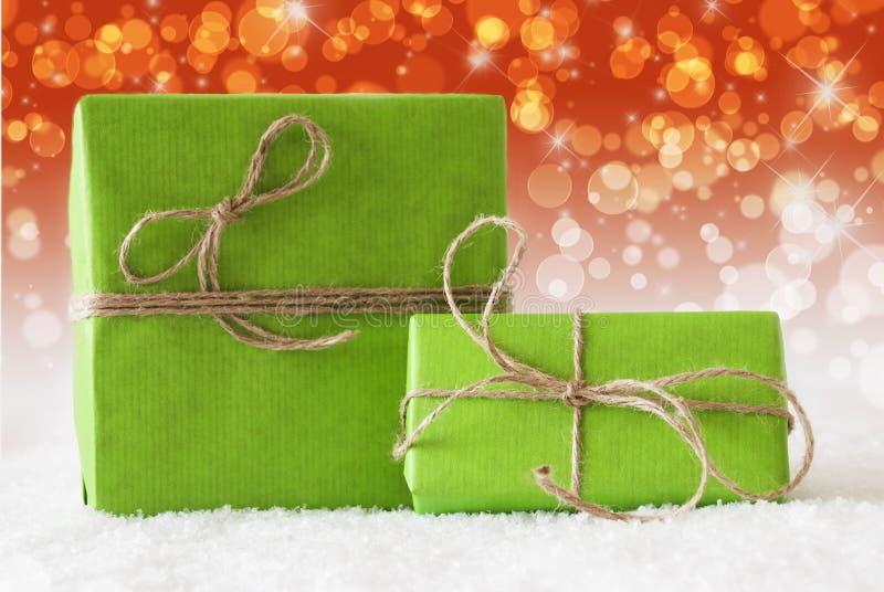 Due regali verdi su neve, effetto rosso complementare di Bokeh immagine stock libera da diritti