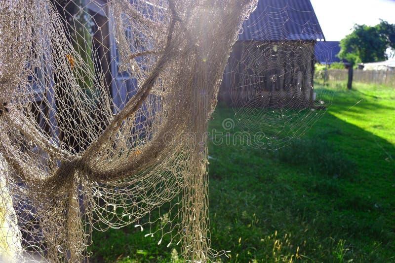 Due reti - pescatore e ragno Patio di estate nel villaggio fotografie stock
