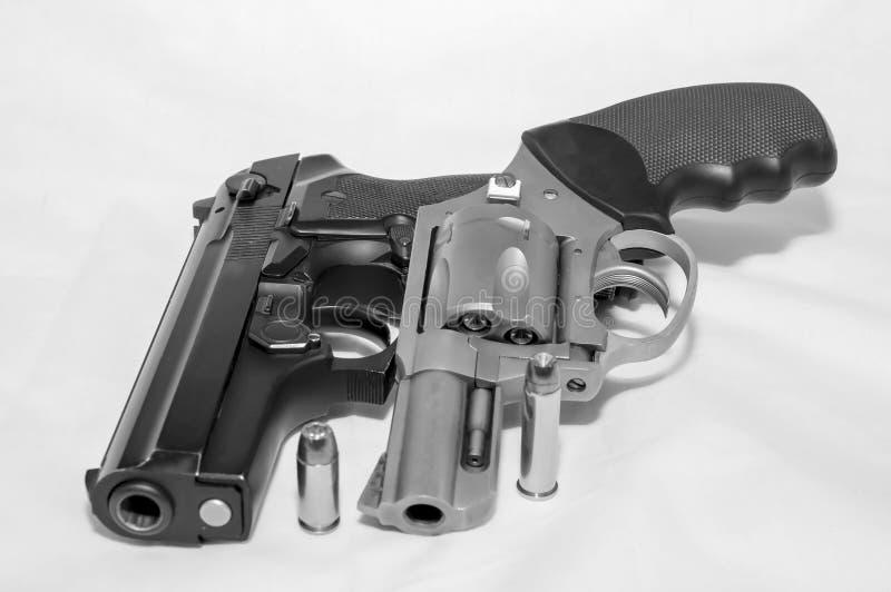 Due rivoltelle, una pistola di 40 calibri e un revolver di 357 magnum con una pallottola per ciascuno fotografia stock