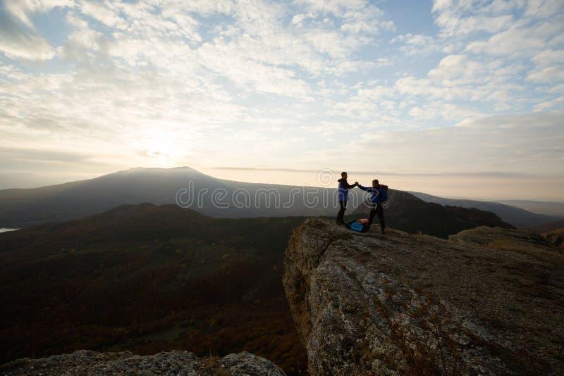 Due scalatori che stanno sul summit sopra le nuvole nel tenersi per mano delle montagne Siluette delle viandanti che celebrano as fotografia stock libera da diritti
