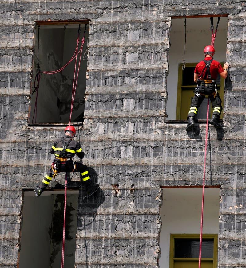 Due scalatori dei pompieri che scalano una casa fotografie stock libere da diritti
