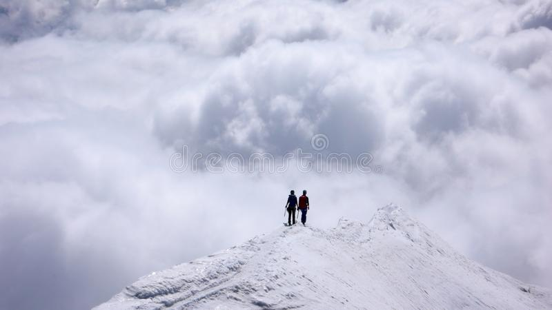 Due scalatori di montagna femminili su una cresta stretta della sommità alta sopra i banchi di nuvole nelle valli qui sotto fotografie stock