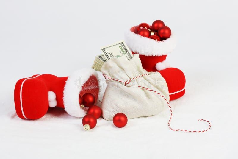 Due scarpe di Santa con le palle rosse di natale della stuoia e Santa insaccano con la pila di soldi immagini stock