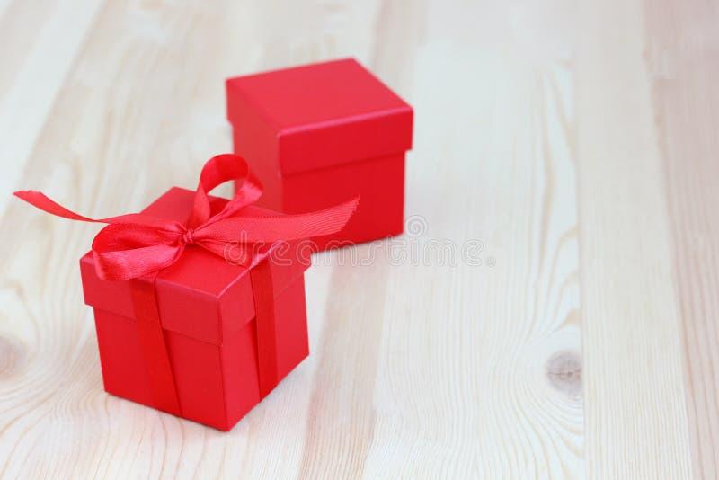Due scatole rosse su una tavola di legno, fuoco selettivo regalo, imballante fotografie stock libere da diritti