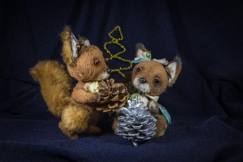 Due scoiattoli con le pigne vicino ad un albero decorativo fotografia stock libera da diritti