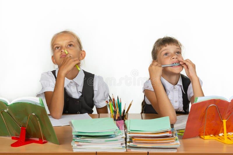 Due scolare pensively e divertenti si siedono alla tavola e cercano fotografia stock libera da diritti