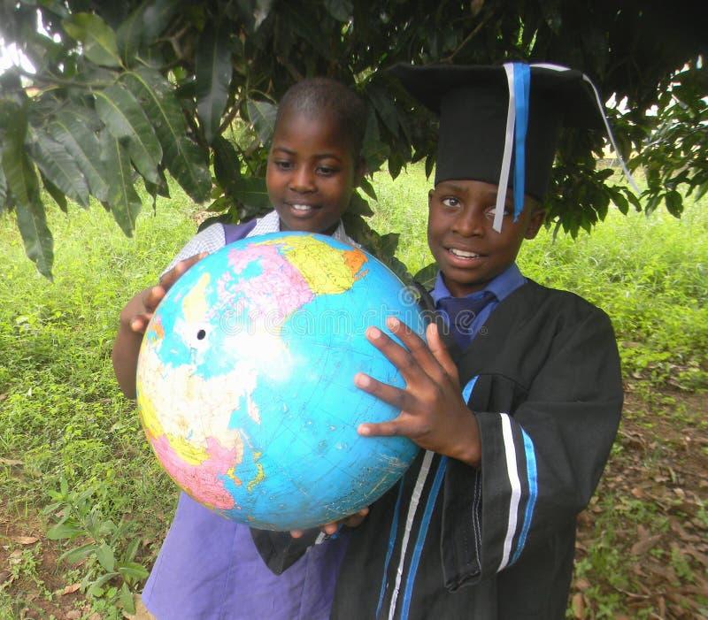 Due scolari che studiano la mappa del globo del mondo all'aperto fotografia stock libera da diritti