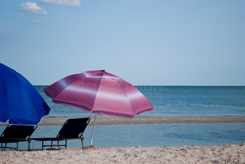 Due sedie di spiaggia e due ombrelli all'aperto prima dell'estate del cielo blu del mare fotografia stock