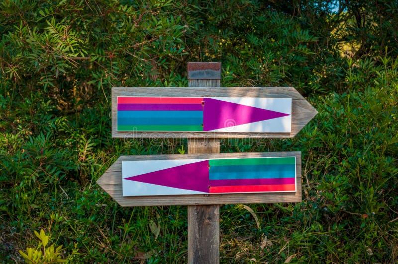 due segni per le direzioni opposte nel parco fotografie stock libere da diritti
