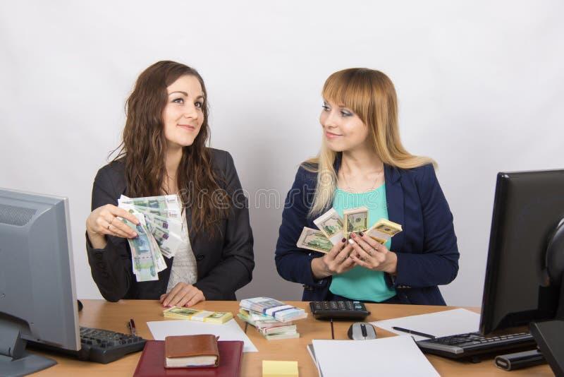 Due segretarie felici stanno discutendo molti soldi, di cui è tenuto nelle mani fotografia stock