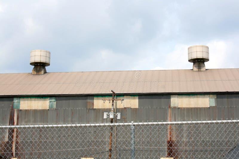 Due sfiati industriali del tetto del metallo con la vista nuvolosa del cielo blu fotografie stock