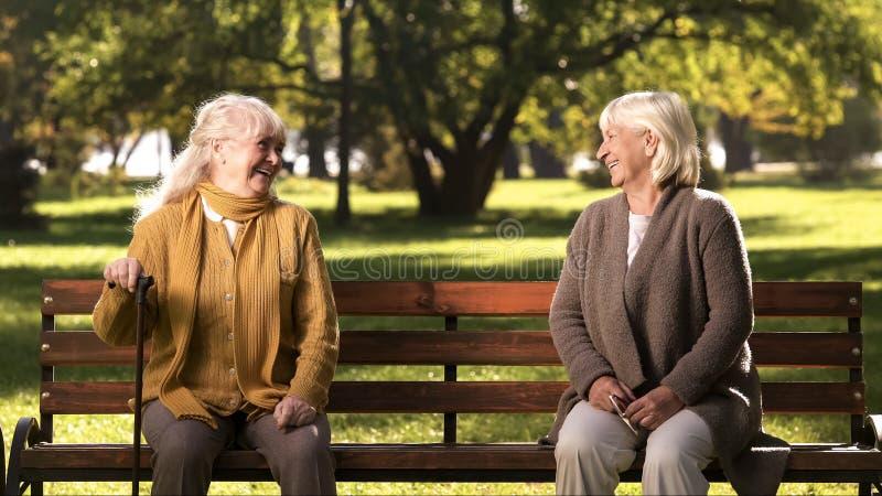 Due signore anziane che ridono e che parlano, sedentesi sul banco in parco, vecchi amici immagini stock libere da diritti