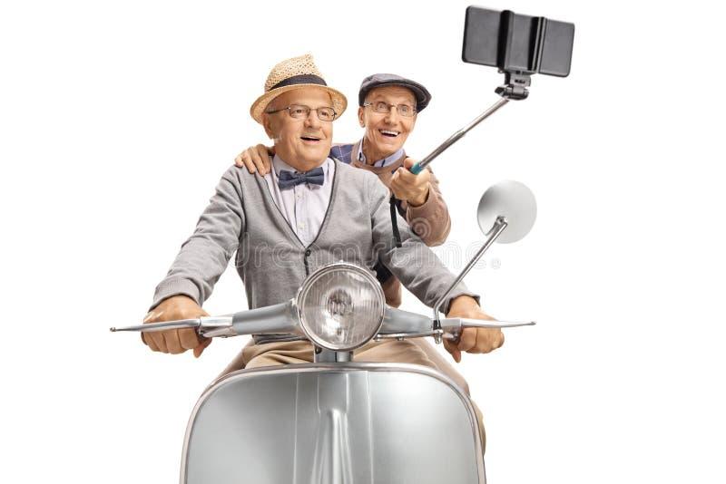 Due signori anziani che prendono un selfie su un motorino d'annata fotografia stock