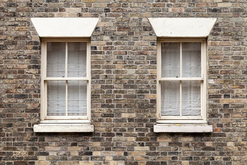 Due simili finestre nella pietra del mattone fotografie stock libere da diritti