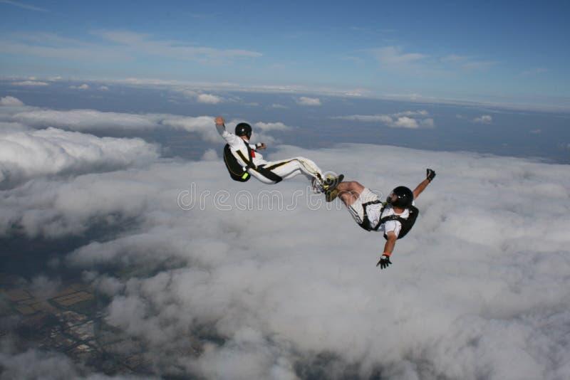 Due skydivers in una seduta posizionano mentre nella caduta libera immagine stock