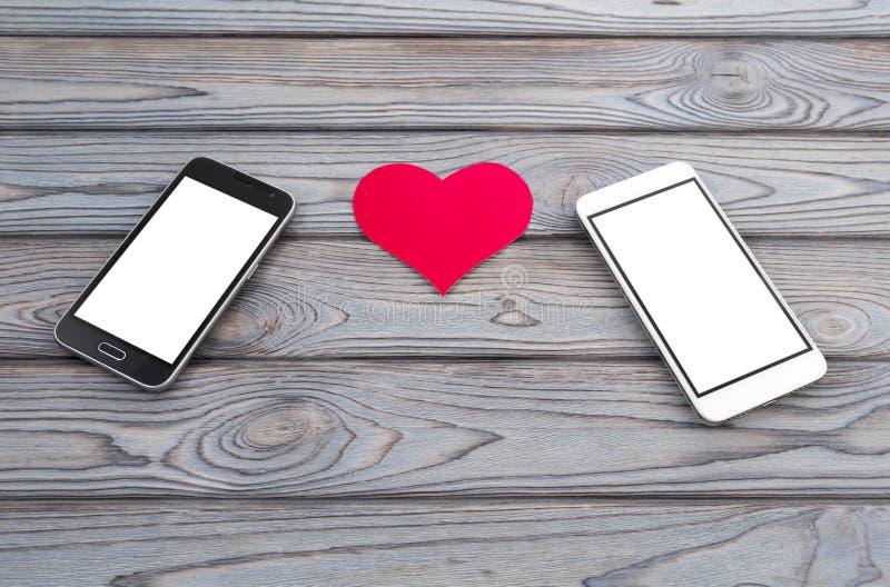 Due smartphones e carte dei cuori sulla tavola di legno fotografie stock