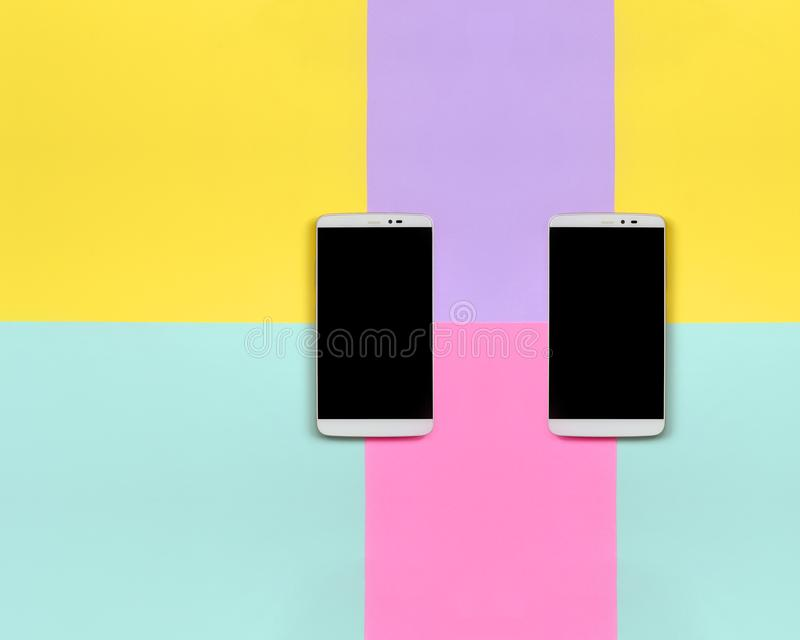Due smartphones moderni con gli schermi neri sul fondo di struttura dei colori blu di modo, gialli, viola e rosa pastelli incarta fotografia stock libera da diritti