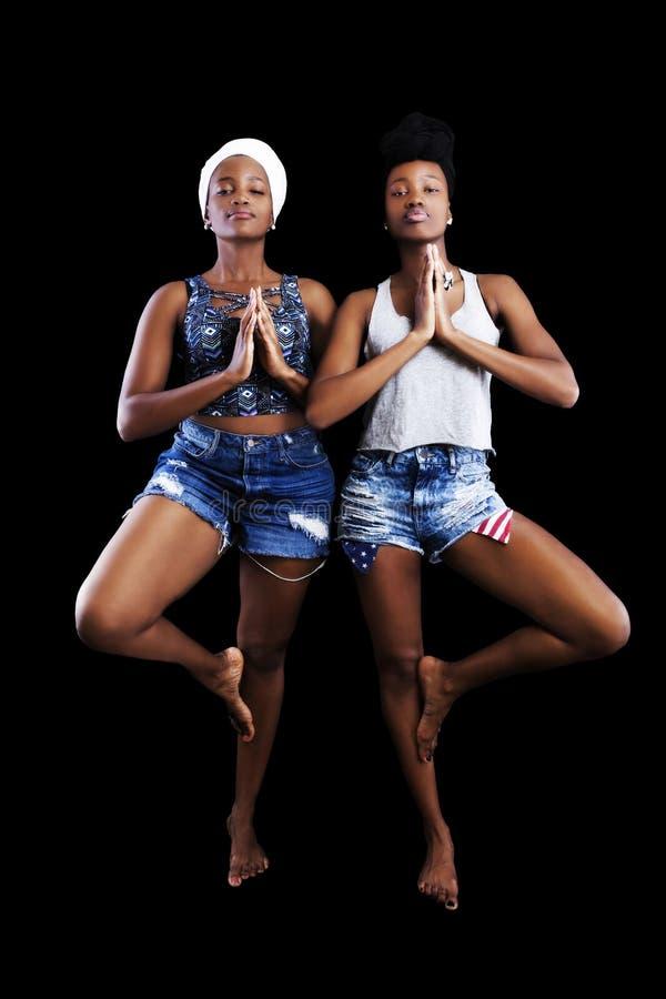 Due Sorelle Africane Americane In Cuffie Sullo Sfondo Oscuro immagine stock