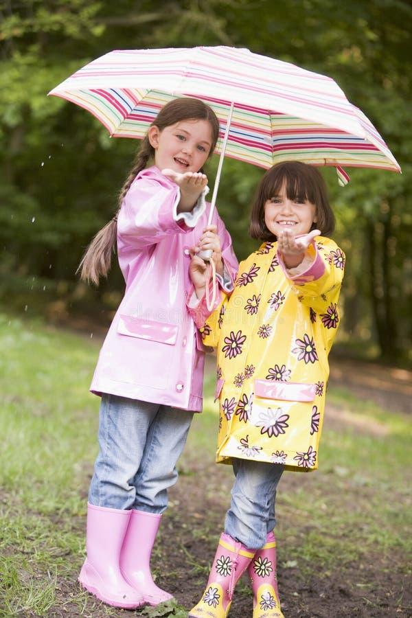 Due sorelle all'aperto in pioggia con sorridere dell'ombrello fotografia stock