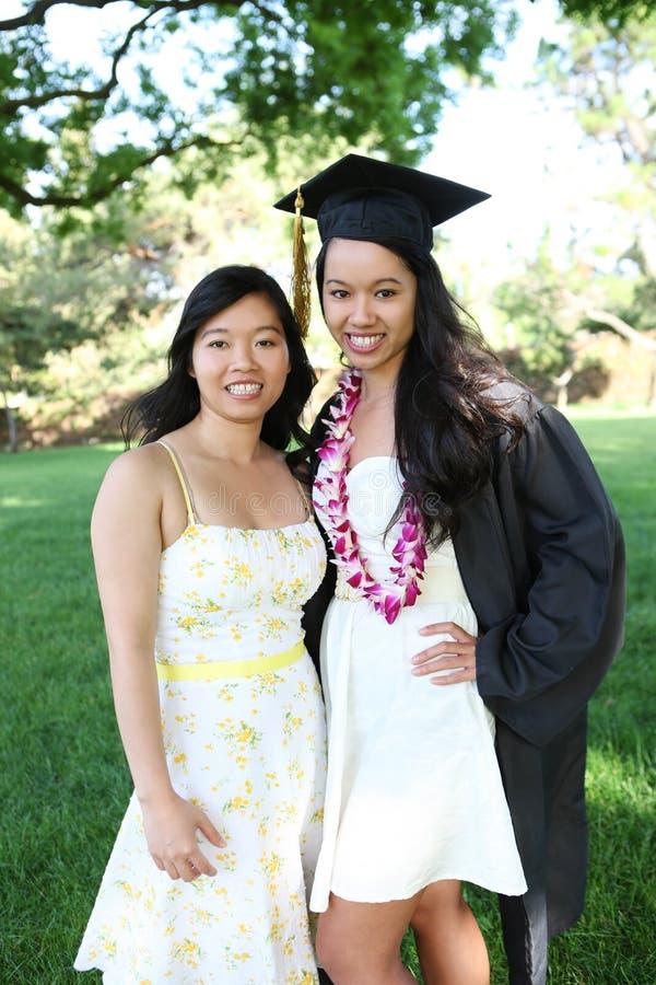 Due sorelle alla graduazione dell'istituto universitario immagine stock libera da diritti