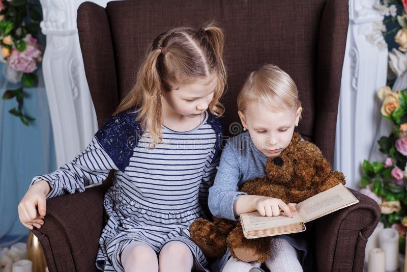 Due sorelle che leggono un libro immagini stock libere da diritti
