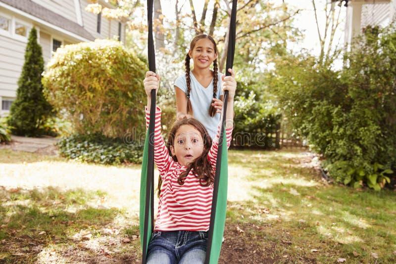 Due sorelle che si divertono sul giardino oscillano a casa fotografie stock
