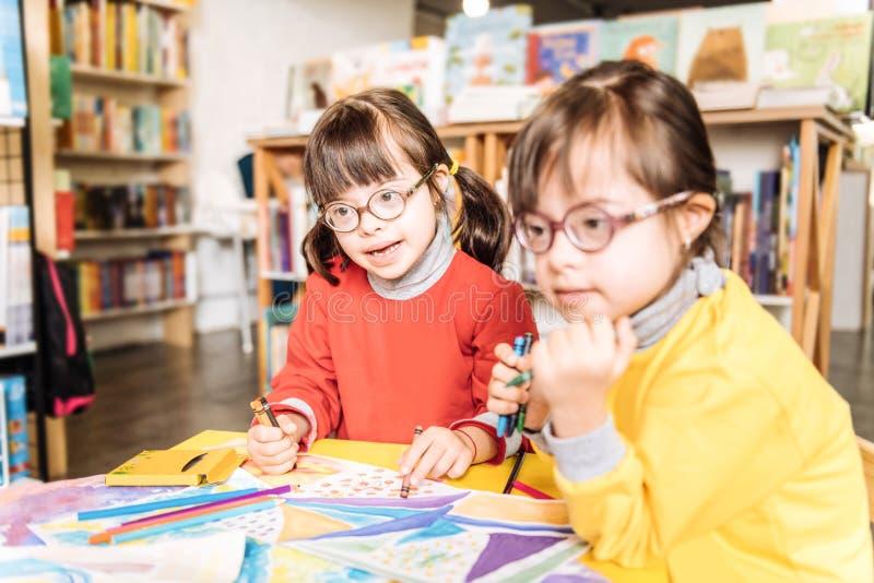 Due sorelle con sindrome di Down leggera che porta i maglioni rossi e gialli fotografia stock