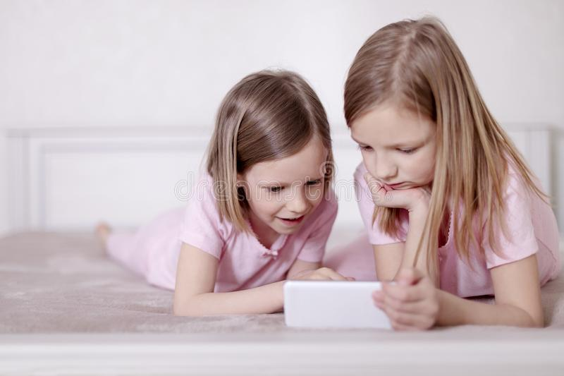 Due sorelle delle bambine in pigiami rosa sul letto che guardano uno smartphone e che leggono un libro elettronico fotografia stock