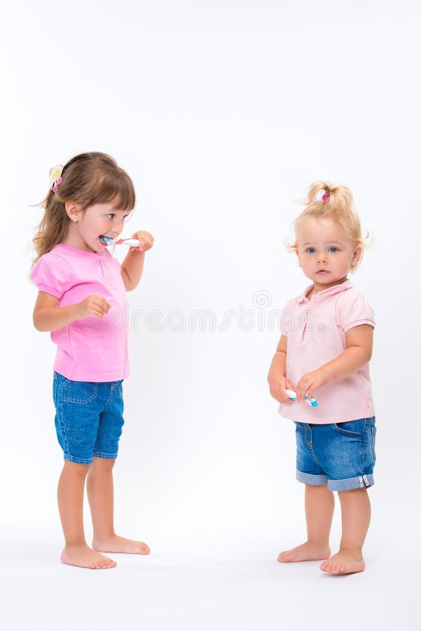 Due sorelle delle ragazze in maglietta rosa con gli spazzolini da denti stanno alla loro altezza completa isolati su fondo bianco immagini stock libere da diritti