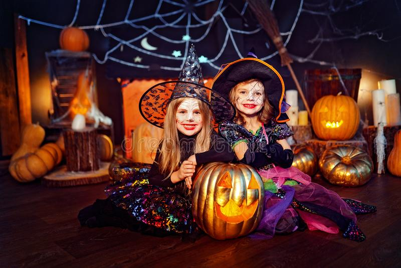 Due sorelle divertenti sveglie celebrano la festa Bambini allegri in costumi di carnevale pronti per Halloween fotografia stock libera da diritti