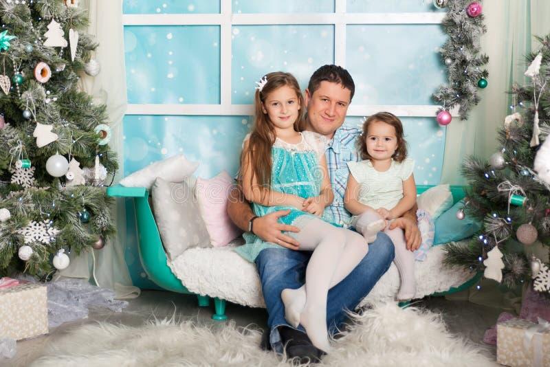 Due sorelle e un padre in decorazioni di Natale fotografia stock libera da diritti